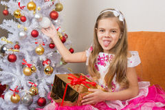 Seven-year girl in beautiful dress sits with a gift and showed language to frame Royalty Free Stock Photography