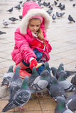 Seven-year girl feeding pigeons with bread in street Royalty Free Stock Images