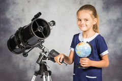 Seven-year girl is happy with the globe in a reflector telescope Royalty Free Stock Photo