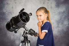 Seven-year girl looks at sky while standing at the telescope Royalty Free Stock Photos