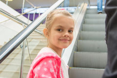Seven-year girl lying down on an escalator in mall with a smile look in the frame Royalty Free Stock Photos