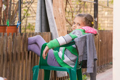 Seven-year girl is resting sitting on chair in the yard and putting his feet on the wooden fence Stock Images