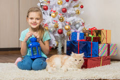 Seven-year girl sits with a cat under the Christmas tree with gifts and smiling happily Royalty Free Stock Photos