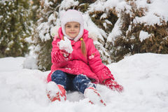 Seven-year girl sitting in the snow and the snow keeps the snow in his hand Royalty Free Stock Photography