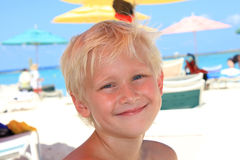 Seven year old blonde boy at the beach. Portrait of a seven year old blonde Caucasian boy at the beach, head and shoulders only, smiling at the camera.  Beach Stock Photo