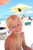 Seven year old blonde boy at the beach. Portrait of a seven year old blonde caucasian boy at the beach, head and shoulders only, smiling at the camera.  Beach Royalty Free Stock Images