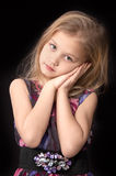 Seven year old blonde girl. Looking pensively in a dress standing  put her hands to the face on a black background Stock Image