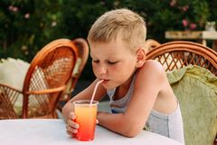 Seven-year-old blonde tanned boy drinking orange non-alcoholic cocktail from a tube in a summer restaurant royalty free stock photo