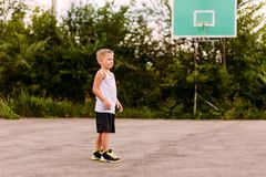 Seven-year-old boy in basketball uniform trains on an open basketball court in the summer. Children and sport, the boy in. A blond seven-year-old boy in royalty free stock image