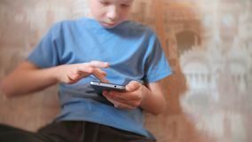 Seven-year-old boy browsing internet on his mobile phone with serious face. Seven-year-old boy browsing internet on his mobile phone with serious face stock video footage