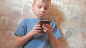 Seven-year-old boy browsing internet on his mobile phone with serious face. Seven-year-old boy browsing internet on his mobile phone with serious face stock video
