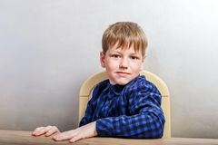 Seven-year-old boy in dark shirt sitting at the table royalty free stock photos