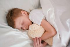 Seven-year-old boy falling asleep hugging toy bear. royalty free stock image