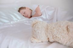 Seven-year-old boy falling asleep with toy bear on bed. royalty free stock photos