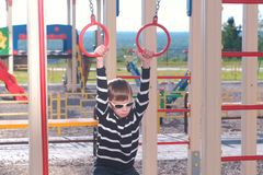 Seven-year-old boy hangs on the gymnastic rings on the Playground. stock image