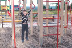 Seven-year-old boy hangs on the gymnastic rings on the Playground. stock photos