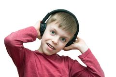 Seven year old boy with headphones singing. On white background stock photography