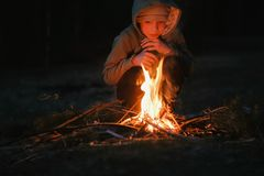 Seven-year-old boy light a fire in the woods. stock photo
