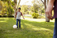 Seven year old boy playing football in a park with dad Royalty Free Stock Images