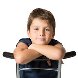 The seven year old boy sits astride a chair. Picture taken on a white background. Very beautiful seven year old boy sits astride a chair Stock Image