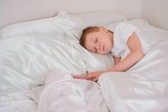 Seven year-old boy sleeping in his bed stock photos