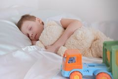 Seven-year-old boy sleeping with his toys bear and plastic car. royalty free stock photo