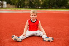 Seven-year-old boy in a sports uniform sits on the red surface of the stadium royalty free stock photography