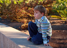 Seven year old boy staring. A seven year old blond haired boy is outdoors and is staring at something. He has brown hair and is wearing a striped shirt and blue Royalty Free Stock Photo