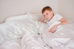 Seven-year-old boy wakes up in his bed under the blanket stock image