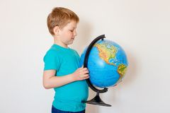 Seven-year-old Caucasian boy holding a large globe stock image