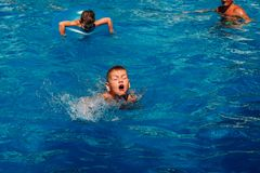 Seven-year-old child learns to swim in the outdoor pool stock photography