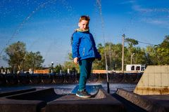 Seven-year-old cute boy in a blue windbreaker and scarf stands near the city fountain stock photos