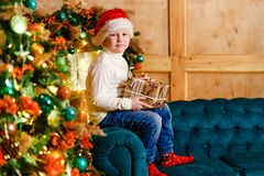 Seven-year-old cute boy in red socks and a hat and jeans sitting on the couch near the Christmas tree with a gift in his hands stock photo