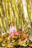 Seven year old girl in the forest. Seven year old girl is sitting on the tree trunk Royalty Free Stock Photo