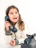 Seven year old girl with old vintage phone before white backgrou Stock Image
