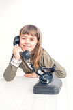 Seven year old girl with old vintage phone before white backgrou Stock Photography