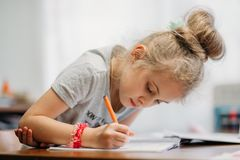 A seven-year-old girl sits at home at a table and writes in a notebook, completing a learning task or repeating lessons. A seven-year-old girl sits at home at a stock images