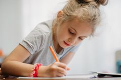 A seven-year-old girl sits at home at a table and writes in a notebook, completing a learning task or repeating lessons. stock photography