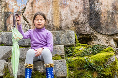 Seven year old girl sitting in the park and holding the umbrella stock images
