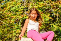 Seven year old girl sitting on the wall. Seven year old girl is sitting on the wall royalty free stock photography