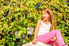 Seven year old girl sitting on the wall Stock Photography