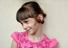 The seven-year-old girl with sweet cherry berries as earrings onears. Portrait royalty free stock photography