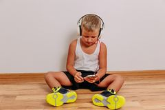 Seven-year-old tanned child listening to music through large full-size headphones on a white background. A boy in bright green. Sneakers sits on the floor and royalty free stock images