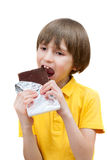 A seven years boy is biting a stick of chocolate royalty free stock photos