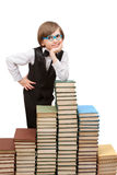 A seven years boy is standing at big stack of books Stock Photography