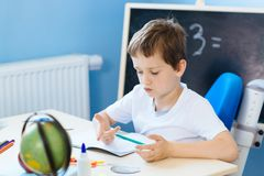 Seven years old boy, counting on fingers. While doing his homework. Back to school royalty free stock photography