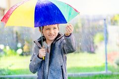 Seven years old boy standing at the rain Royalty Free Stock Photography