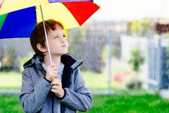 Seven years old boy standing at the rain. With colorful umbrella royalty free stock images