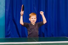 The seven years old child is happy to win in table tennis. On blue background royalty free stock photos