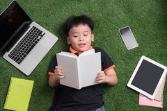 Seven years old child reading a book lying on the grass stock photography